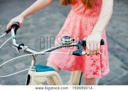 Close up hands of a young girl in pink dress, pressed handbrake on vintage bicycle