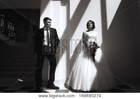 portrait of beautiful bride and stylish groom. Woman in wedding white dress and man in black suit. concept of happy marriage and strong family. black-and-white geometry and shadows