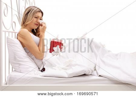 Sad woman crying and wiping her tears while lying in bed isolated on white background