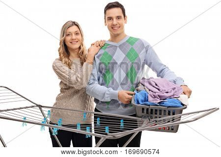 Happy couple standing behind a clothing rack dryer with the man holding a laundry basket full of clothes isolated on white background