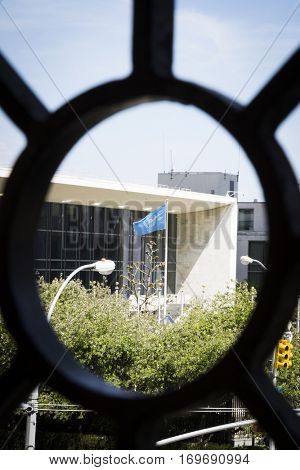 NEW YORK - APR 30 2016: The blue and white flag of the United Nations seen through a bullseye shaped iron fence in Ralph Bunche Park across 1st Avenue on the East side of Manhattan.