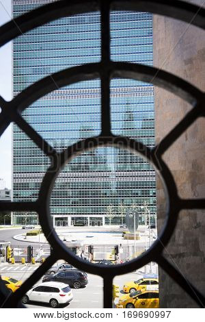 NEW YORK - APR 30 2016: The front of the United Nations building seen through a bullseye shaped iron fence above Ralph Bunche Park across 1st Avenue on the East side of Manhattan.