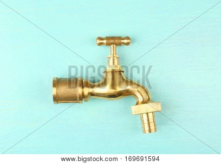 Brass faucet on color wooden background