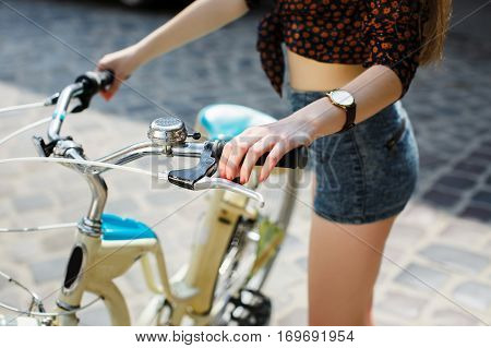Girl hands holding a bicycle handlebar. Close-up. Outdoors.