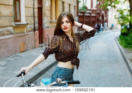 Portrait of attractive girl with perfect slim body holding bicycle handlebar wearing denim shorts and shirt. Looking at camera. On the streets of the old city.