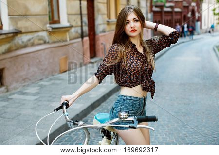 Portrait of attractive girl with perfect slim body holding bicycle handlebar wearing denim shorts and shirt. Looking somewhere. On the street.