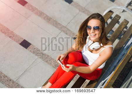 Top view of young pretty brunette with mobile phone sitting on bench in summer park
