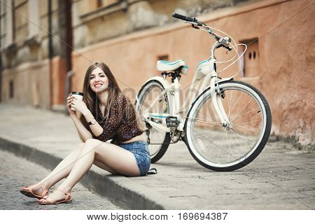 Cute young woman with long fair hair wearing on dark blouse and blue shorts is drinking coffee and smiling on tiled pavement with bicycle on a background on the street of old European city .