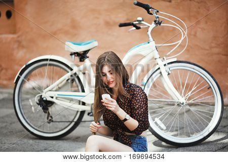 Young girl with long fair hair wearing on short dark blouse and shorts sitting on tiled pavement and looking at her mobile phone with bicycle on a background on the street of old city .