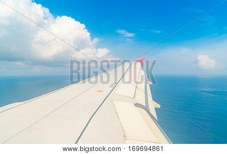 Airplane descending over a blue ocean to maldives island