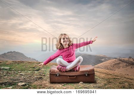 Cute blonde child in pink outfit simulating to fly while sitting on a big brown luggage in the nature