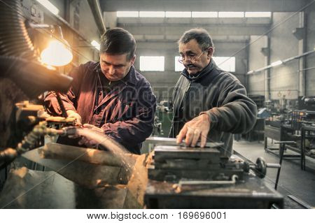 Two men doing induction hardening in a factory
