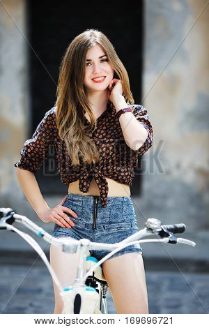 Beautiful girl wearing on dark blouse and blue shorts with long straight fair hair is posing on the bicycle and smiling on the street of old city.