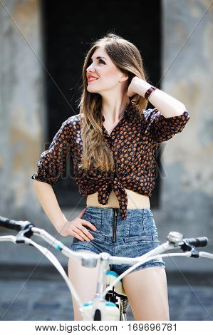Young attractive girl wearing on dark blouse and blue shorts with long straight fair hair is sitting on the bicycle and looking at right on the street of old city.