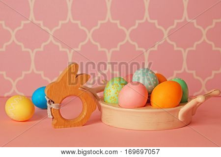 Easter eggs and rabbit figure on pink table