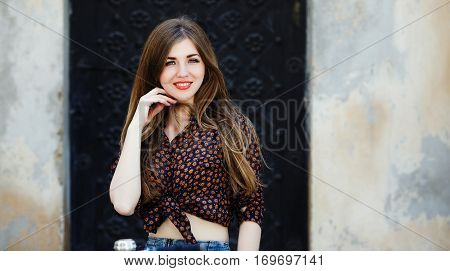 Smiling young woman wearing on dark blouse with long straight fair hair is looking at the camera on the street of old European city