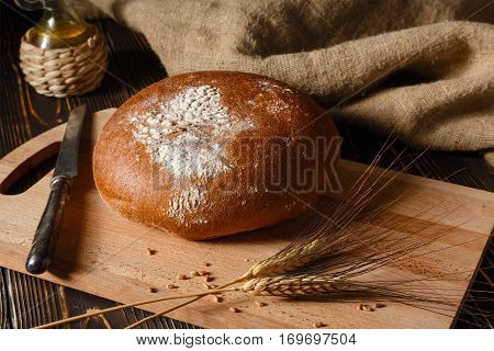 Rural rye bread lies on a table nearby ear of rye lie.