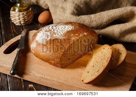 Rye bread lies on a breadboard two pieces of bread nearby