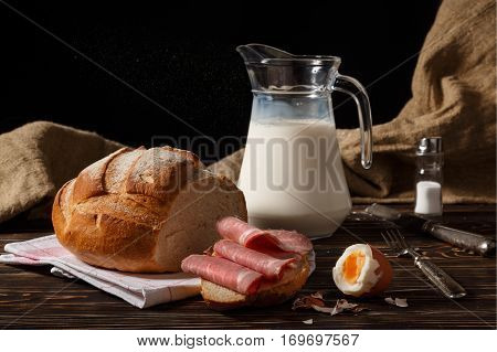 Rural breakfast on a table. Jug with milk the peeled egg meat on a piece of white bread.