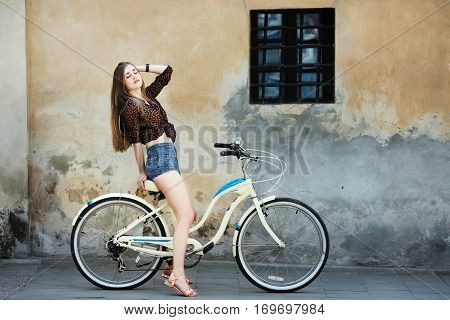 Young girl with long fair hair wearing on dark blouse and blue shorts is posing on the bicycle on the old wall background, on the street of European city