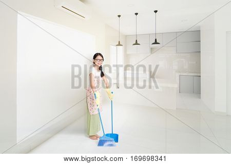 Young Asian housewife sweeping floor with broom and dustpan , cleaning house.