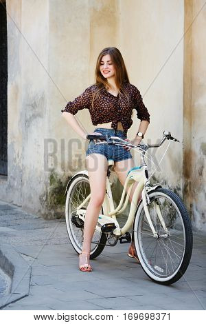 Happy girl with long fair hair, wearing on dark blouse and blue shorts, is sitting on the bicycle on the street of old European city