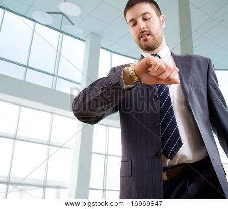 Businessman looking at wrist  watch in office