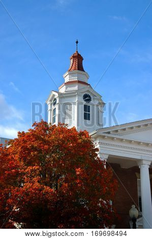 County courthouse in North Arkansas has copper top brick and white wooden construction. Autumn foliage covers tree by courthouse with brilliant orange.