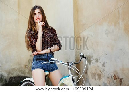 Passionate young woman with long straight fair hair wearing on dark blouse and blue shorts is posing on the bicycle on the old wall background