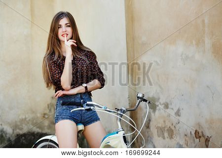 Smiling young woman with long straight fair hair wearing on blouse and blue shorts is posing on the bicycle on the old wall background
