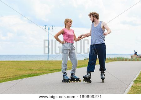 Young Couple Holding Hands While Rollerblading