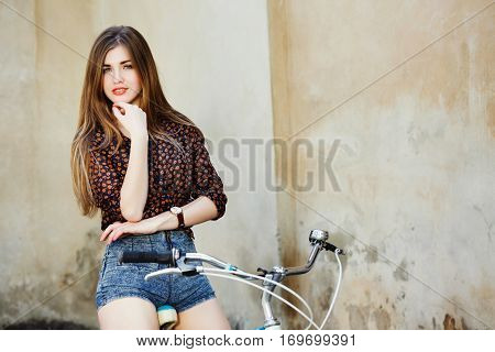 Lovely young woman with long straight fair hair wearing on dark blouse and blue shorts is sitting on the bicycle on the old wall background