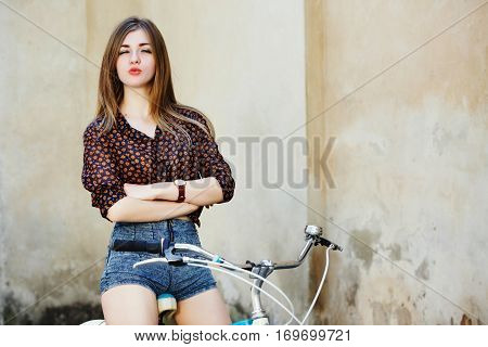 Happy young woman with long fair hair wearing on short blouse and shorts is posing on the bicycle on the old wall background, waist up