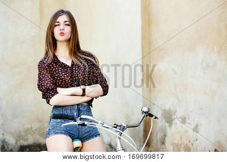 Charming girl with long fair hair wearing on short blouse and shorts is posing on the bicycle on the old wall background, waist up