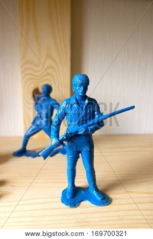 miniature toy soldier on wood background, close-up