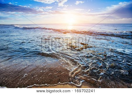 Sunset on the sandy beach, the sun disappears over the horizon at sea
