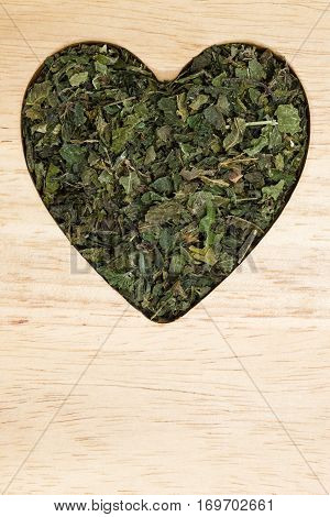 Healthy food healing herbs alternative herbal medicine concept. Dried herb nettle leaves in form of heart on wooden board with copy space