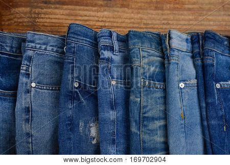 Row of blue jeans on wooden.