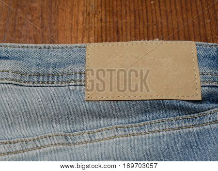 Blank leather jeans label sewed on a blue jeans on wooden background