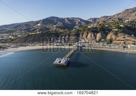 Aerial of the historic Malibu Pier, beaches and the Santa Monica Mountains on the Southern California Pacific Coast.