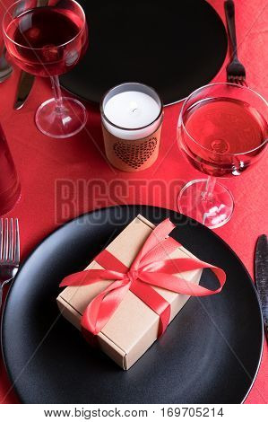 Romantic dinner table setting on Valentine's Day. Gift or present on a plate. Date in restaurant. Wine and candle.