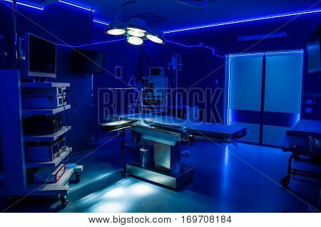 Equipment And Medical Devices In Modern Operating Room. Blue Lighted.