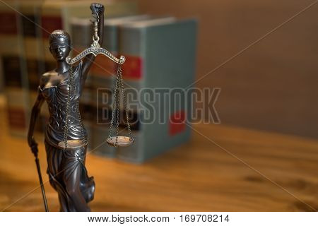 Burden of proof - legal law concept image with Scales of justice and row of law books in background. Hazy light from right good for text copy.