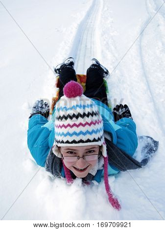 Little Girl sledding down snowy hill on sled fast speed