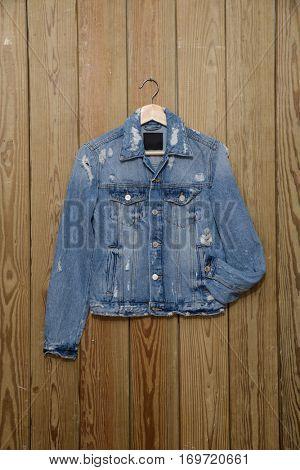 A blue denim jean shirt -hanger on wooden background
