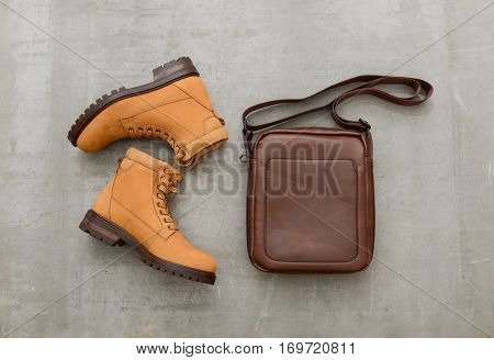 Men's casual outfits with boots shoes and handbag on gray background