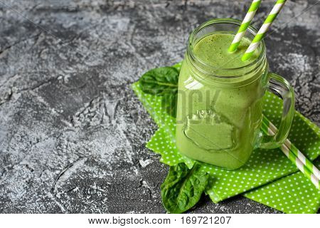 Detox drink - Green smoothie with spinach apple and yogurt on a concrete background. Organic food.