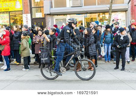 Chicago IL United States - February 5 2017: Chicago police officer riding his bicycle during the Chinese New Year Parade in Chinatown Chicago IL.