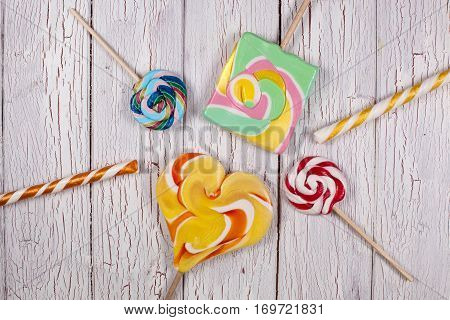 Lollypops making a shape of a sun on a white wooden background