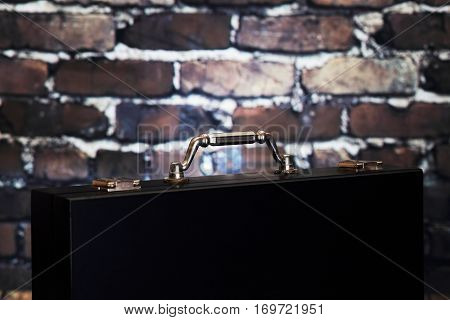 Close up top briefcase on brick background. Black suitcase with shiny handle. Closeup of black case for business paper